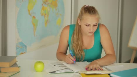Young-Girl-Sitting-At-Table-Writing-And-Eating-Apple