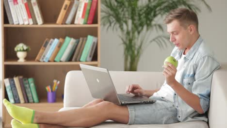 Young-Man-Relaxing-On-Sofa-With-Laptop-And-Eating-Apple