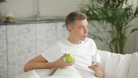 Young-Men-Sitting-On-Sofa-Eating-Apple-And-Using-Cellphone