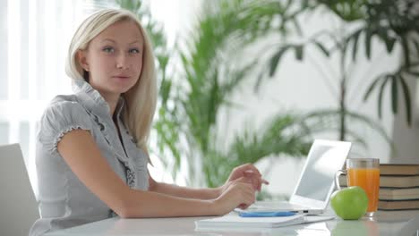 Young-Woman-Sitting-At-Table-Using-Laptop-And-Smiling-At-Camera