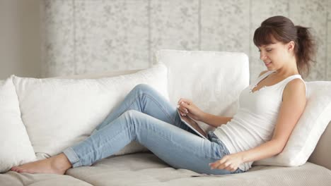 Young-Woman-Sitting-On-Sofa-With-Touchpad-And-Credit-Card-And-Smiling