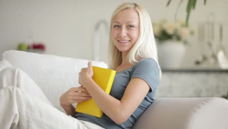 Young-Woman-With-Book-Closing-It-Holding-It-To-Her-Chest-And-Smiling