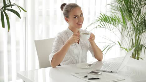 Atractiva-Mujer-Sentada-A-La-Mesa-Con-Una-Taza-De-Café