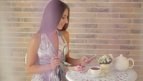 Beautiful-Girl-Sitting-At-Cafe-And-Using-Cellphone-And-Eating-Cake