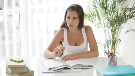 Beautiful-Girl-Sitting-At-Table-And-Writing-In-Notebook
