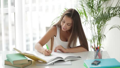 Beautiful-Girl-Sitting-At-Table-Reading-Book-And-Writing-In-Notebook