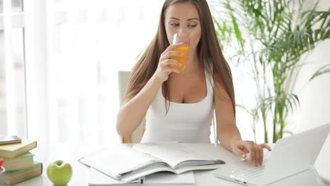 Beautiful-Girl-Sitting-At-Table-Using-Laptop-And-Drinking-Juice