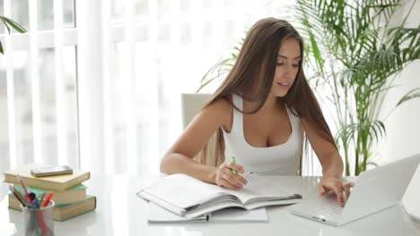 Beautiful-Girl-Sitting-At-Table-Using-Laptop-And-Writing-In-Notebook