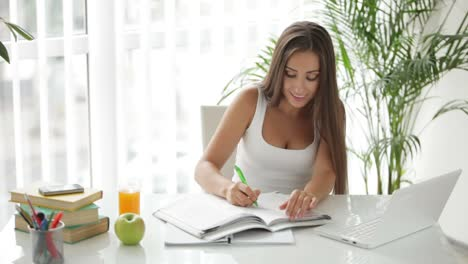 Beautiful-Girl-Sitting-At-Table-Using-Laptop-Writing-In-Notebook-And-Drinking