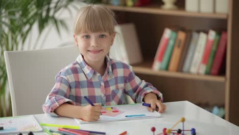 Beautiful-Little-Girl-Sitting-At-Desk-Drawing-With-Colored-Pencils-And-Smiling