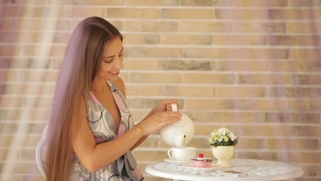 Beautiful-Young-Girl-Sitting-At-Cafe-And-Pouring-Tea-Into-Cup