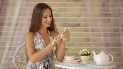 Beautiful-Young-Girl-Sitting-At-Cafe-And-Using-Cellphone