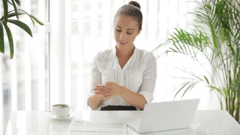 Businesswoman-Sitting-At-Table-Using-Laptop-And-Cellphone