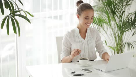 Businesswoman-Sitting-At-Table-With-Cup-Of-Cofee-And-Using-Laptop