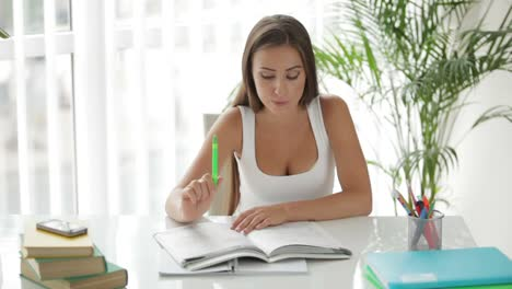 Charming-Girl-Sitting-At-Table-And-Writing-In-Notebook-03