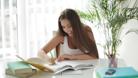 Charming-Girl-Sitting-At-Table-Reading-Book-And-Writing-In-Notebook