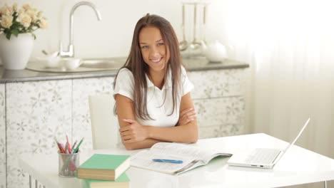 Encantadora-Niña-Sentada-A-La-Mesa-Con-Libros-Y-Laptop-Escribiendo-En-El-Libro-De-Trabajo-Mirando-02