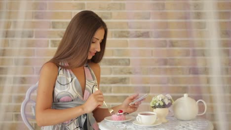 Charming-Young-Girl-Sitting-At-Cafe-And-Using-Cellphone-And-Eating-Cake