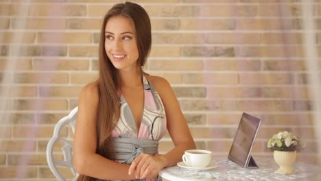 Charming-Young-Girl-Sitting-At-Cafe-With-Cup-Of-Tea-And-Tablet