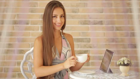 Charming-Young-Girl-Sitting-At-Cafe-With-Cup-Of-Tea-And-Touchpad