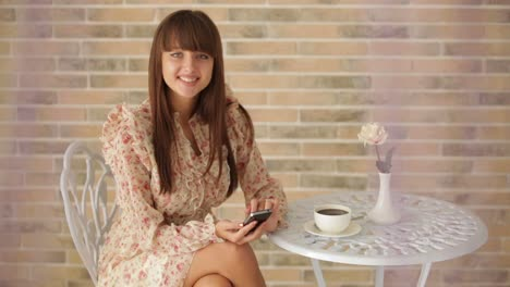 Charming-Young-Woman-Sitting-At-Cafe-Using-Cellphone-And-Drinking-Tea
