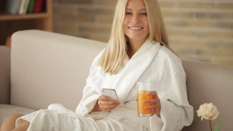 Cheerful-Girl-In-Bathrobe-Sitting-On-Sofa-With-Tray-Of-Food-Using-Cellphone