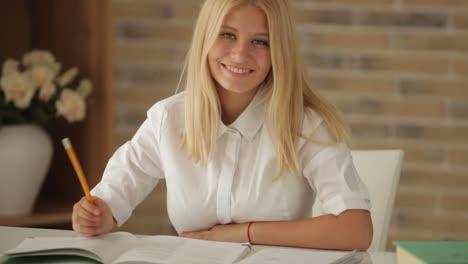 Fröhliches-Mädchen-Das-Am-Tisch-Mit-Büchern-Sitzt-Und-Das-Schreiben-In-Notizbuch-Und-SM-Studiert