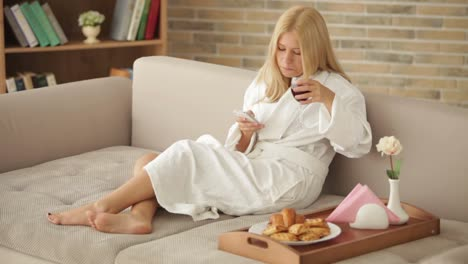 Cheerful-Girl-Wearing-Bathrobe-Sitting-On-Sofa-Using-Cellphone-Holding-Glass