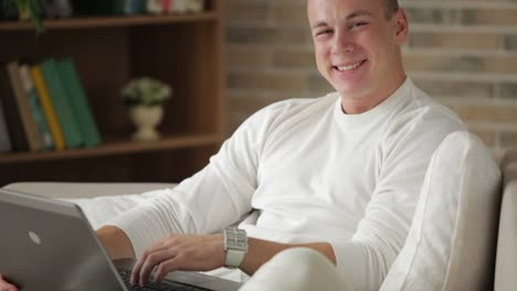 Cheerful-Guy-Sitting-On-Sofa-Using-Laptop-And-Smiling-At-Camera