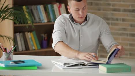 Alegre-Estudiante-Masculino-Sentado-En-La-Mesa-Y-Estudiar-Con-Libros