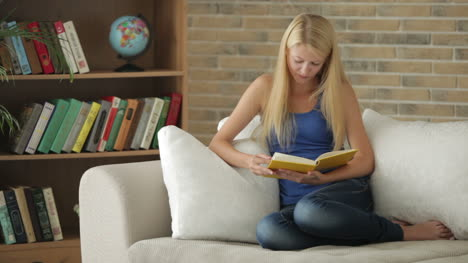 Cute-Blonde-Girl-Sitting-On-Sofa-Reading-Book-Looking-At-Camera-And-Smiling