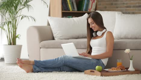 Cute-Girl-In-Headset-Sitting-On-Floor-And-Using-Laptop