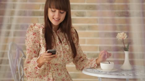 Cute-Girl-Sitting-At-Cafe-Holding-Cellphone-And-Stirring-Coffee