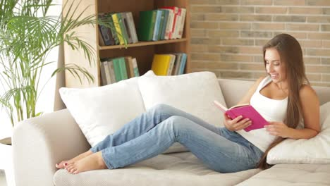 Cute-Girl-Sitting-On-Couch-Reading-Book-And-Looking-At-Camera-With-Smile