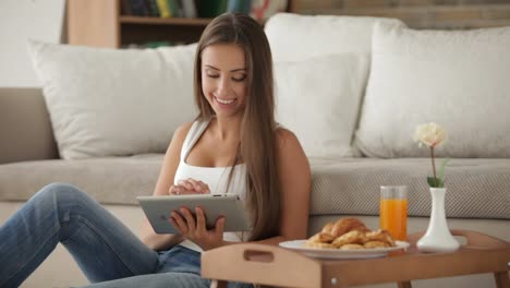 Cute-Girl-Sitting-On-Floor-Using-Touchpad-And-Smiling