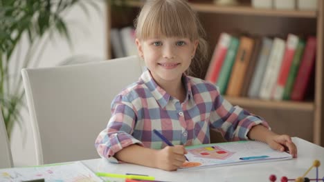Cute-Little-Girl-Sitting-At-Table-Drawing-With-Colored-Pencils-And-Showing