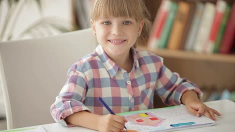 Funny-Little-Girl-Drawing-With-Colored-Pencils-And-Smiling-At-Camera