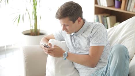 Apuesto-Joven-Sentado-En-El-Sofá-Con-Teléfono-Móvil-Y-Sonriendo-A-La-Cámara