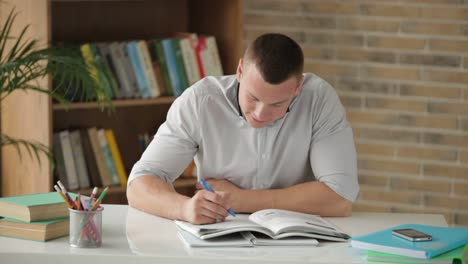 Männlicher-College-Student-Der-Am-Tisch-Sitzt-Und-In-Ein-Notizbuch-Schreibt-Und-Lächelt-Als-Er-Kam-