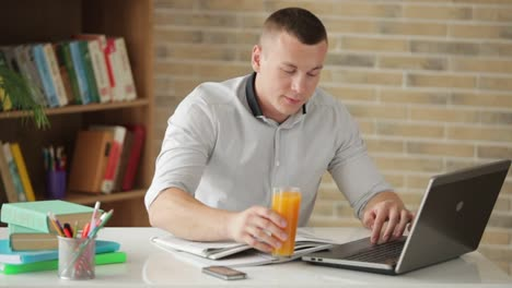 Male-Student-Sitting-At-Desk-Studying-And-Drinking-Juice