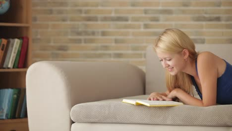 Pretty-Girl-Lying-On-Sofa-Reading-Book-Looking-At-Camera-And-Smiling-Panning