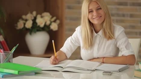 Hübsches-Mädchen-Das-Am-Tisch-Mit-Büchern-Sitzt-Und-Im-Notizbuch-Schreibt-Und-Lächelt
