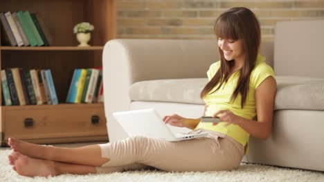 Pretty-Girl-Sitting-On-Floor-With-Laptop-And-Holding-Credit-Card