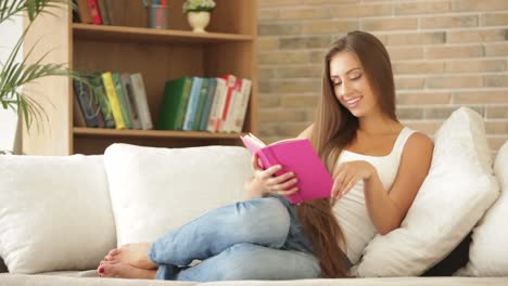 Pretty-Girl-Sitting-On-Sofa-Reading-Book-Closing-It-And-Smiling