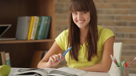 Pretty-Student-Girl-Sitting-At-Desk-And-Writing-In-Notebook