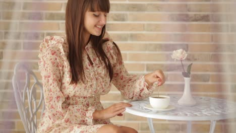 Pretty-Young-Woman-Sitting-At-Cafe-And-Stirring-Coffee