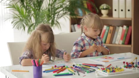 Two-Cute-Little-Girls-Sitting-At-Desk-Drawing-And-Smiling-At-Camera