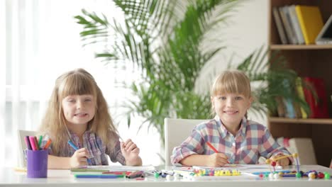 Two-Cute-Little-Girls-Sitting-At-Desk-Drawing-With-Colored-Pencils-And-Smiling