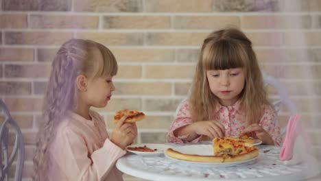 Two-Cute-Little-Girls-Sitting-At-Table-At-Cafe-Eating-Pizza-And-Smiling