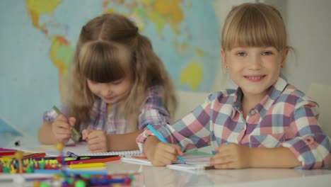 Two-Funny-Little-Girls-Sitting-At-Desk-Drawing-With-Colored-Pencils